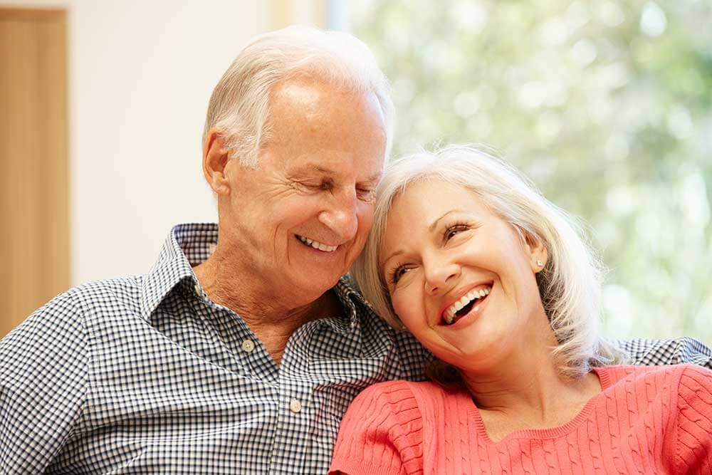 An older couple are sitting next to each other and smiling. The man has his arm around the woman.
