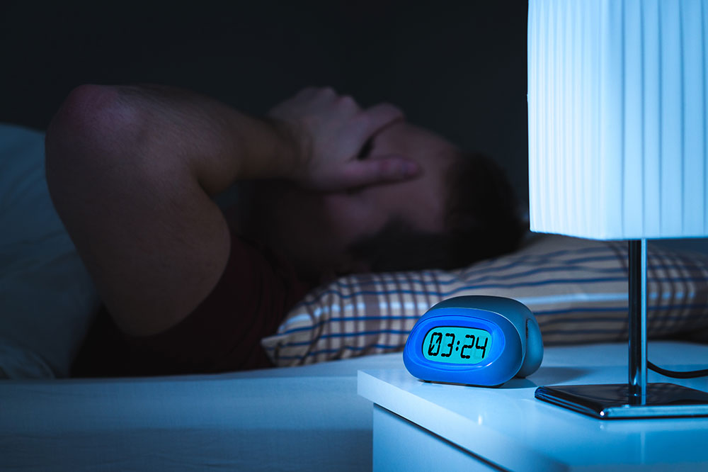 A man is in bed. His hand is covering his face in exhaustion. A clock is next to him on a nightstand that says 3:24.
