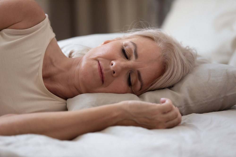 A woman with white hair lies on her side asleep in a white bed. She is wearing a white shirt, and her arm is resting near her head.