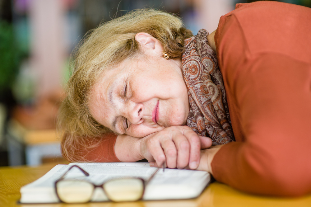 An older woman is asleep on a book. She is wearing a scarf, an orange top, and her glasses are resting nearby.